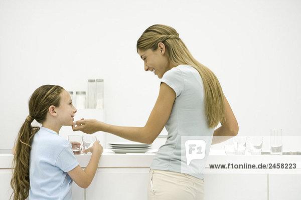 Mutter und Tochter in der Küche  Frau hält Mädchenkinn  beide lächelnd