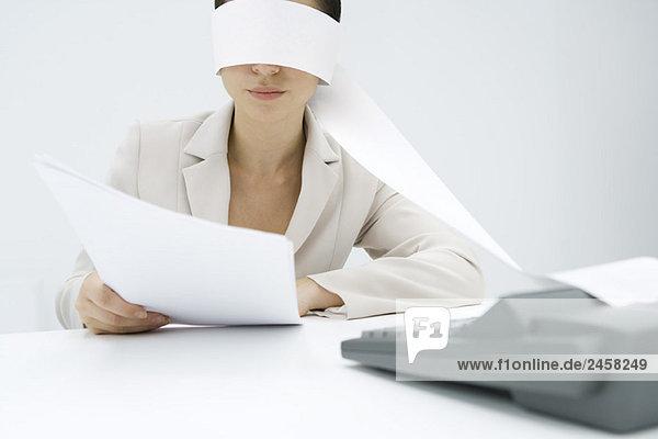 Frau am Schreibtisch sitzend  Klebeband von einer Addiermaschine um den Kopf gewickelt  Dokument haltend