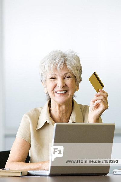 Seniorin am Schreibtisch sitzend  mit Kreditkarte  mit Laptop  lächelnd vor der Kamera