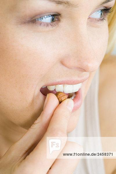 Frau isst eine Nuss  schaut weg  Kopfschuss  Porträt