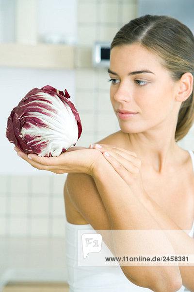 Frau  die einen Kopf aus Radicchio-Salat betrachtet und hält. Frau, die einen Kopf aus Radicchio-Salat betrachtet und hält.