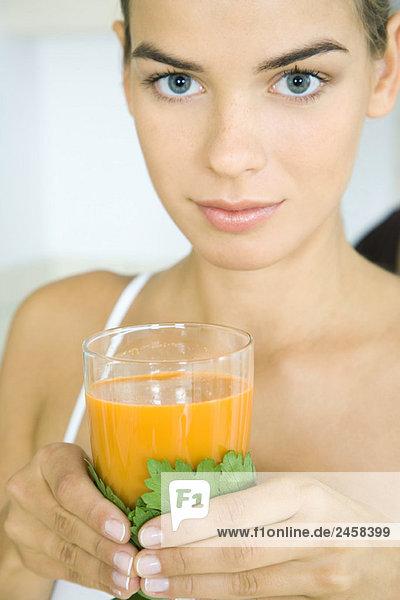 Junge Frau mit einem Glas Gemüsesaft  Blick auf Kamera  Kopf und Schultern Junge Frau mit einem Glas Gemüsesaft, Blick auf Kamera, Kopf und Schultern