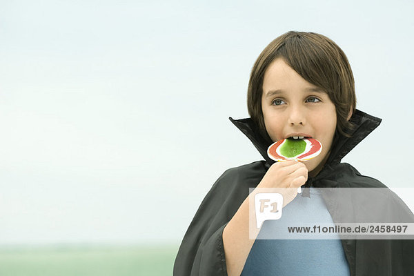 Boy wearing vampire cape  eating large lollipop  portrait