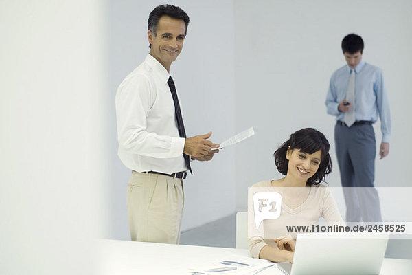 Berufstätige im Büro  Mann steht und hält Dokument  Frau sitzt vor dem Laptop