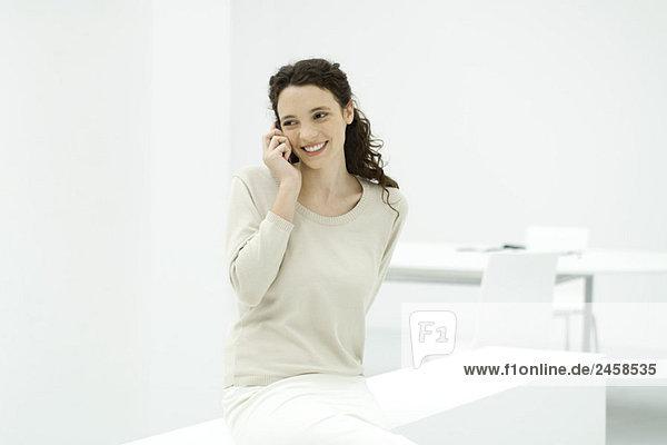Frau im Büro  mit dem Handy  lächelnd