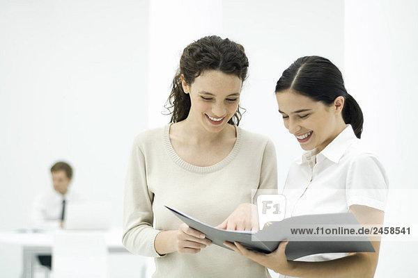 Weibliche Kollegen schauen sich gemeinsam das Dokument an  lächelnd