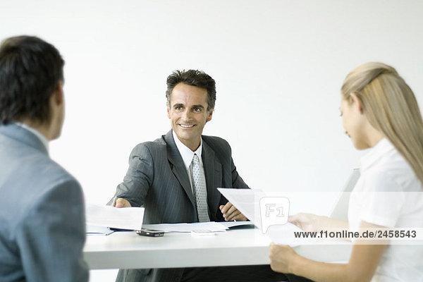Geschäftsmann im Gespräch mit Ehepaar  lächelnd