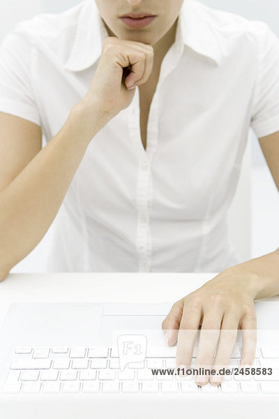 Woman in front of keyboard  hand under chin  cropped view