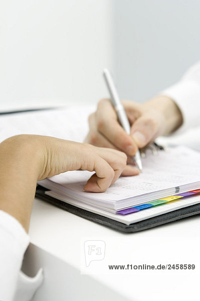 Person pointing at date in agenda  another person writing  cropped view of hands
