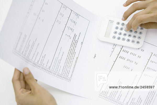 Person holding document  using calculator  cropped view of hands