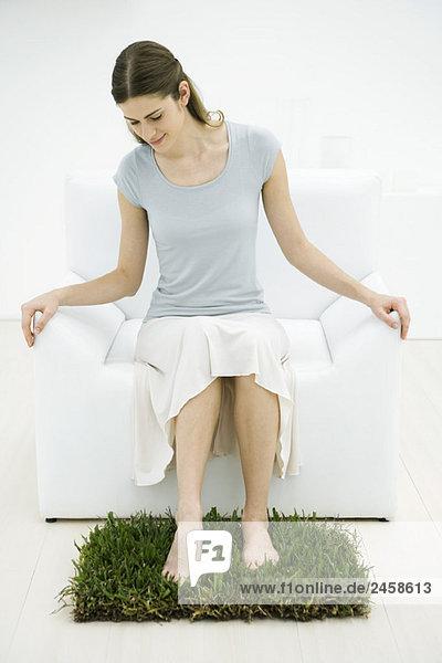 Frau im Sessel sitzend  Füße auf Rasenfläche  drinnen