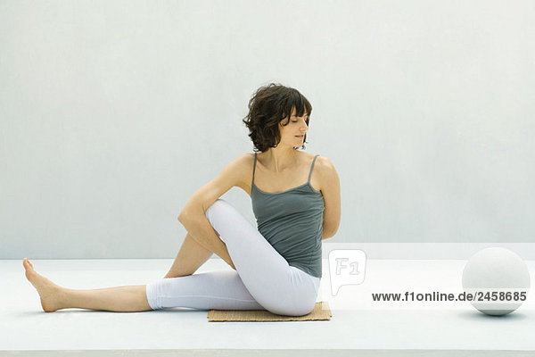Frau macht Yoga auf dem Boden  Ball in der Nähe