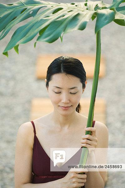 Frau hält Handflächenblatt über den Kopf  Augen geschlossen  lächelnd