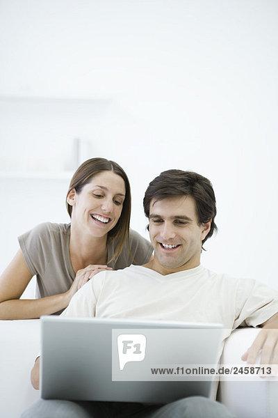 Paar Blick auf Laptop  Mann  sitzend in Sessel  Frau über die Schulter gelehnt