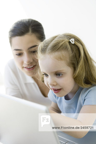 Mother and young daughter looking at laptop computer together  smiling