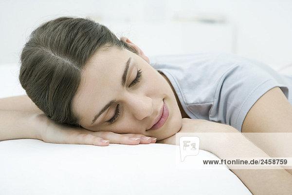 Frau liegend auf Magen  Ruhelosigkeit Kopf auf Armen  Augen geschlossen