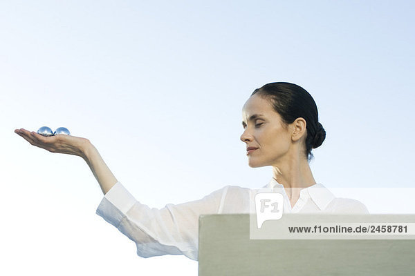 Frau hält aus Yin Yang Bällen in Handfläche Frau hält aus Yin Yang Bällen in Handfläche