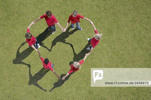 Gruppe von Kindern hält hände in Herzform formation