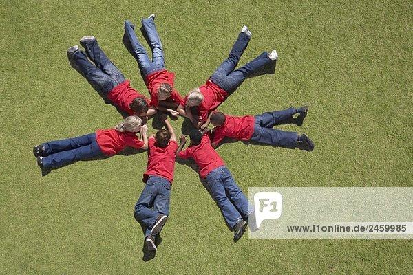 Gruppe von Kindern Verlegung auf Gras in Circle-formation