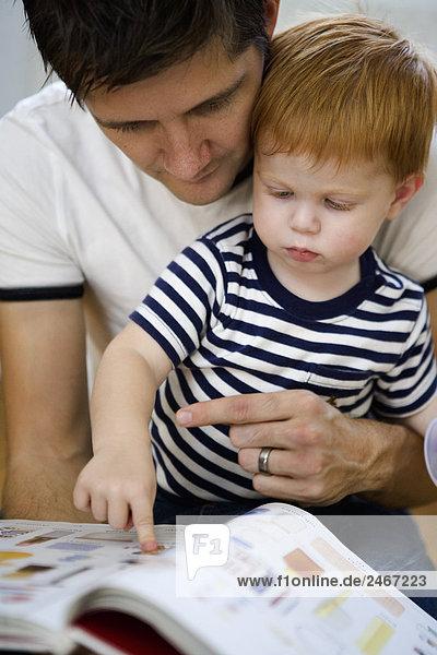 Vater und Sohn ein Buch Schweden zu lesen.