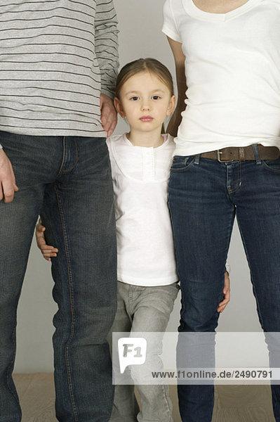 Mädchen steht zwischen seinen Eltern  fully_released