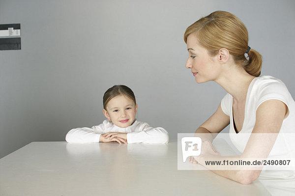 Mutter und Tochter sitzen an einem Tisch  fully_released