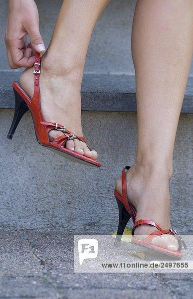 Female Hand Korrektur der Anfall von ihren rote high Heels-Sandalen