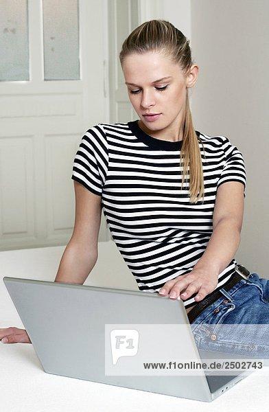 Frau sitzen auf dem Bett mit laptop