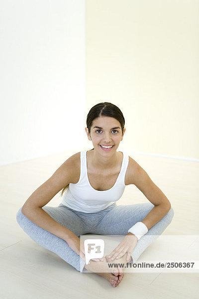 Junge Frau sitzt auf dem Boden  streckt sich  lächelt in die Kamera.