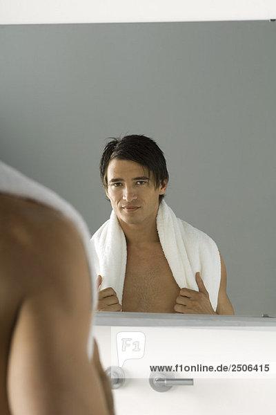Nackter Mann schaut in den Spiegel  lächelt in die Kamera  Handtuch über die Schultern geschleudert.