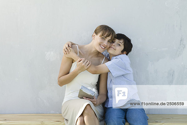 Mother and son embracing  woman holding gift  both smiling at camera