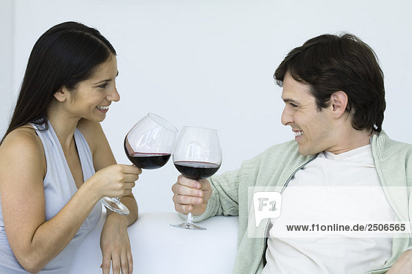 Couple sitting on couch,  clinking wine glasses,  smiling at each other