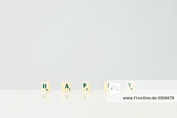 Wortspiel-Fliesen  die das Wort glücklich buchstabieren.