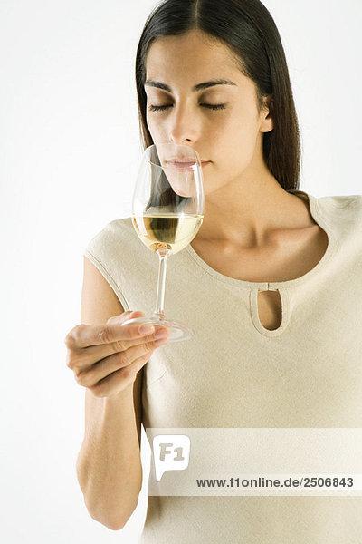 Frau riecht ein Glas Weißwein  Augen geschlossen Frau riecht ein Glas Weißwein, Augen geschlossen
