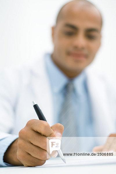 Arzt schreibt ein Rezept  Fokus auf die Hand im Vordergrund