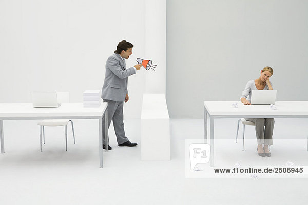Vorgesetzter schreit Mitarbeiter mit Megaphon an  Frau sitzt mit Laptop  umgeben von zerknittertem Papier