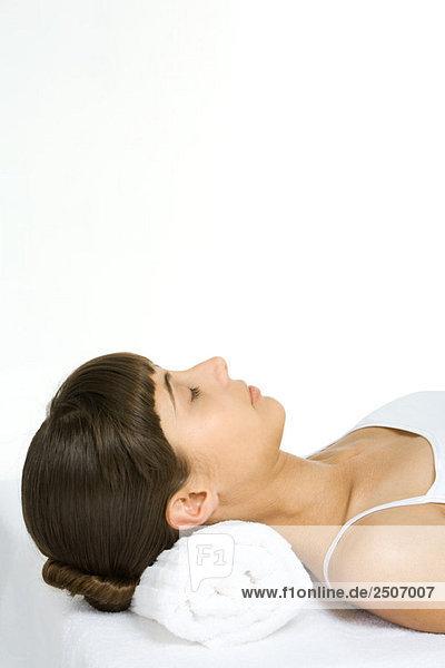 Frau auf dem Rücken liegend mit geschlossenen Augen  mit Handtuch als Kopfkissen  abgeschnittene Ansicht