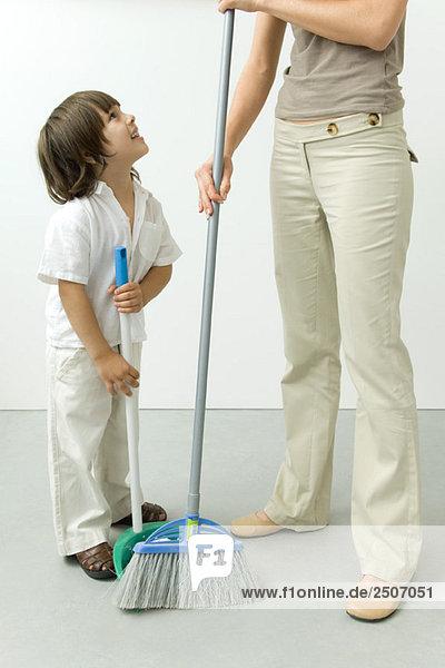 Kleiner Junge  der seiner Mutter hilft  den Boden zu kehren.