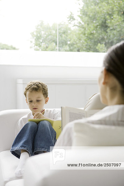 Junge sitzt auf der Couch  schreibt im Buch  Frau liest Buch im Vordergrund