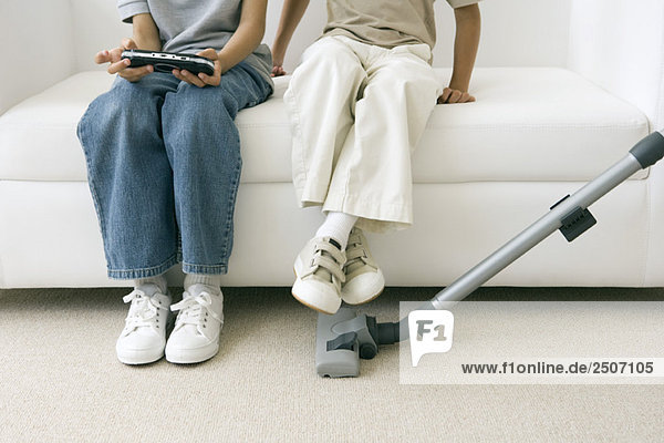 Two children sitting on sofa as parent vacuums  one playing handheld video game  cropped view