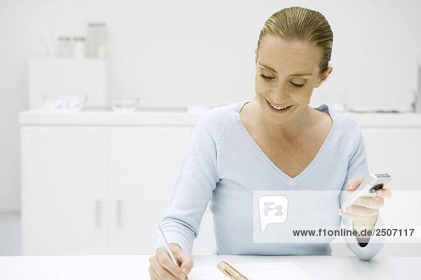 Frau schreibt in Notizbuch und hält Handy