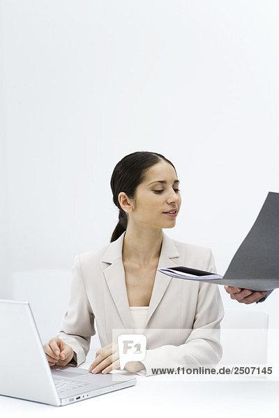 Frau  die sich eine Mappe ansieht  die für sie offen gehalten wird  mit einem Laptop.