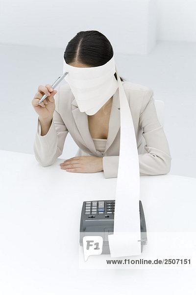 Frau sitzend mit um den Kopf gewickeltem Maschinenband  Stift an der Stirn haltend