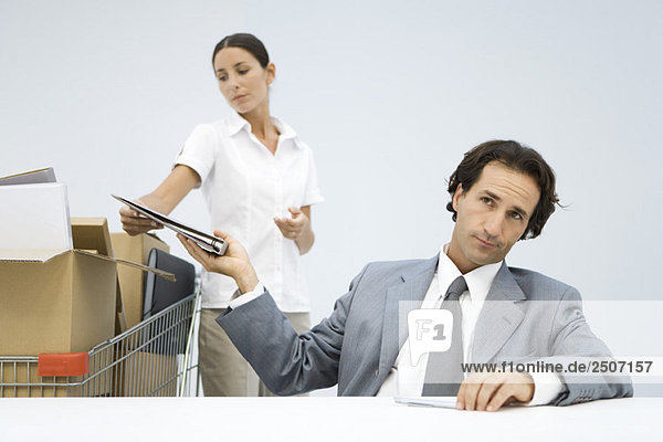 Man handing binder back to assistant  shopping cart full of boxes nearby