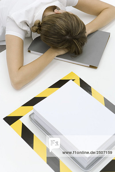 Woman sitting with her head down near a stack of paper surrounded by black and yellow tape