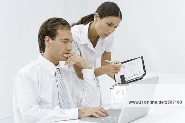 Professioneller Mann mit Laptop  Assistent  der über die Schulter schaut und die Agenda hält.