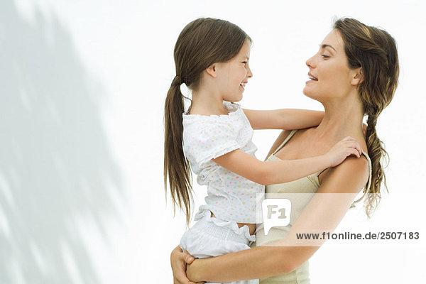 Mutter hält und umarmt Tochter  beide lächeln sich an  Seitenansicht