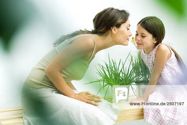 Frau und Tochter riechenden Blütenzweig zusammen Frau und Tochter riechenden Blütenzweig zusammen