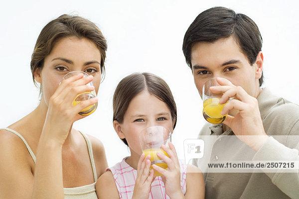 Familie trinkt Orangensaft  alle mit Blick auf die Kamera