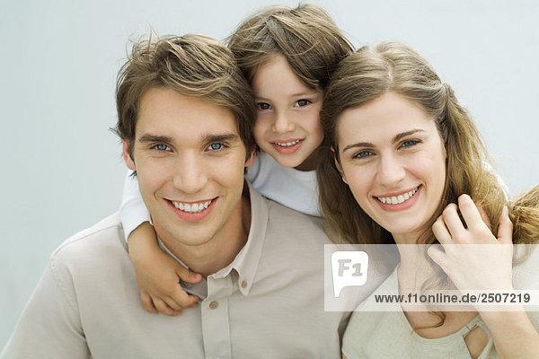 Kleiner Junge legt seine Arme um die Schultern seiner Eltern  lächelt in die Kamera  Porträt
